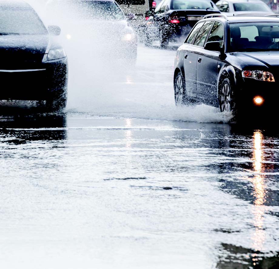 Flooded road with cars splashing by